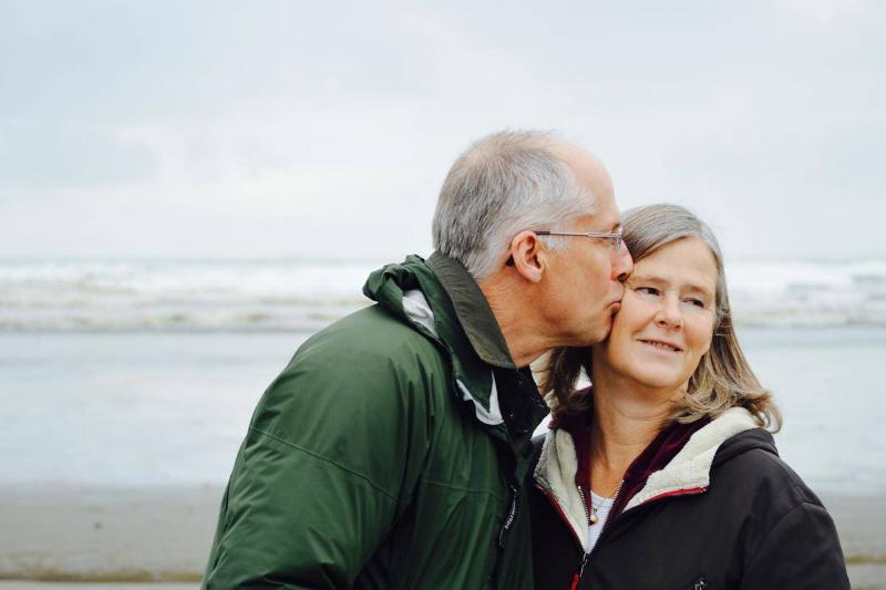 older man kisses woman on the cheek at the beach