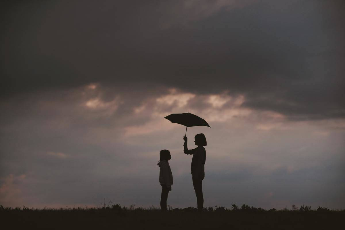 person holds umbrella over someone else
