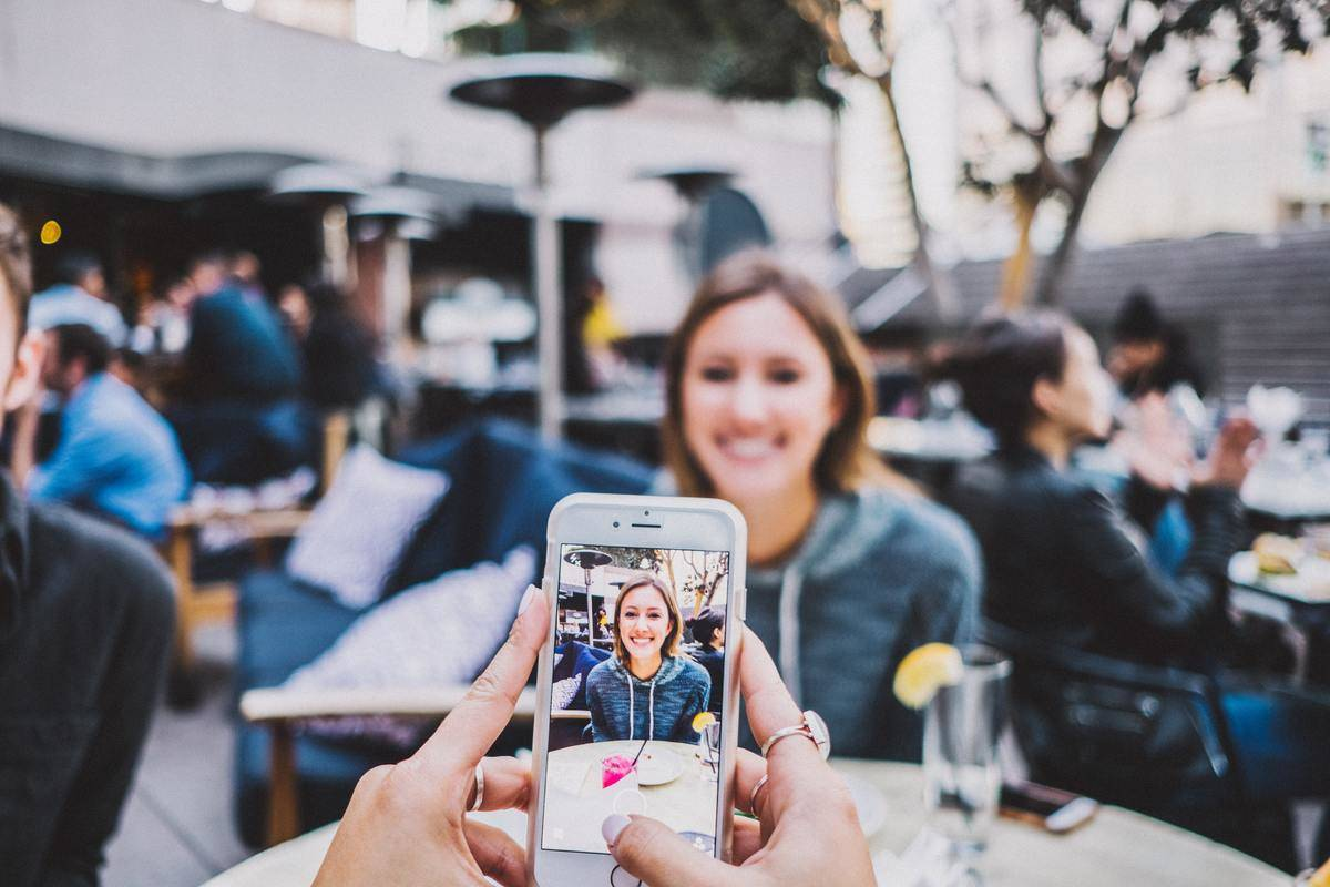person taking photo of woman on other side of the table