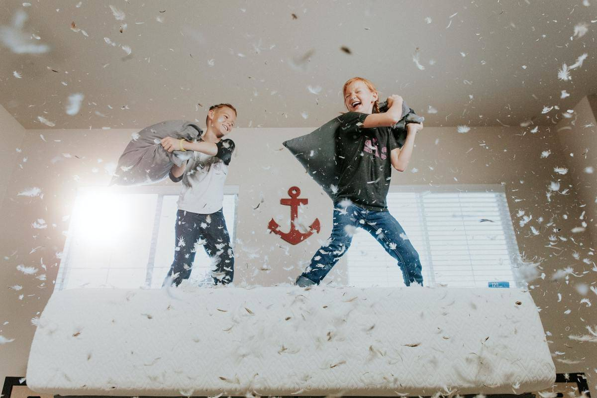 two young boys having a pillow fight