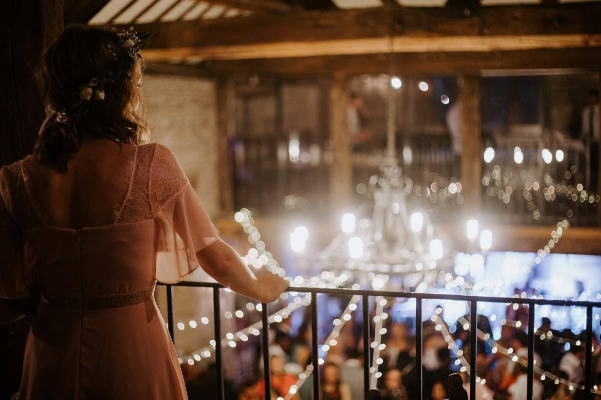 woman overlooking people dancing at wedding reception
