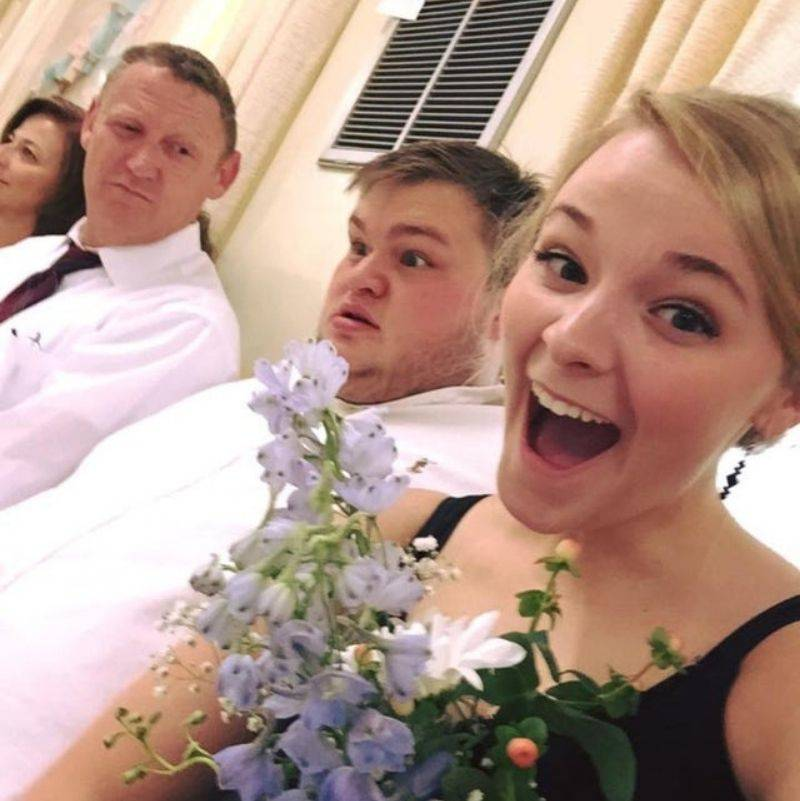 woman taking picture of herself with the bride's flowers and her boyfriend is making a funny face behind her