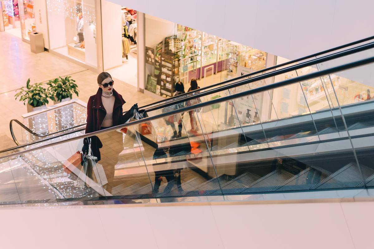 woman riding on escalator at shopping mall holding shopping bags