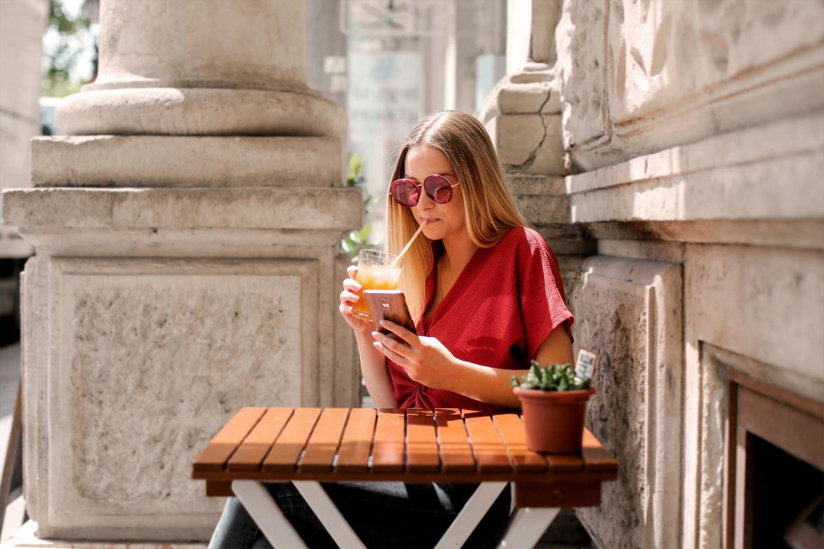 woman sipping their drink while on the phone