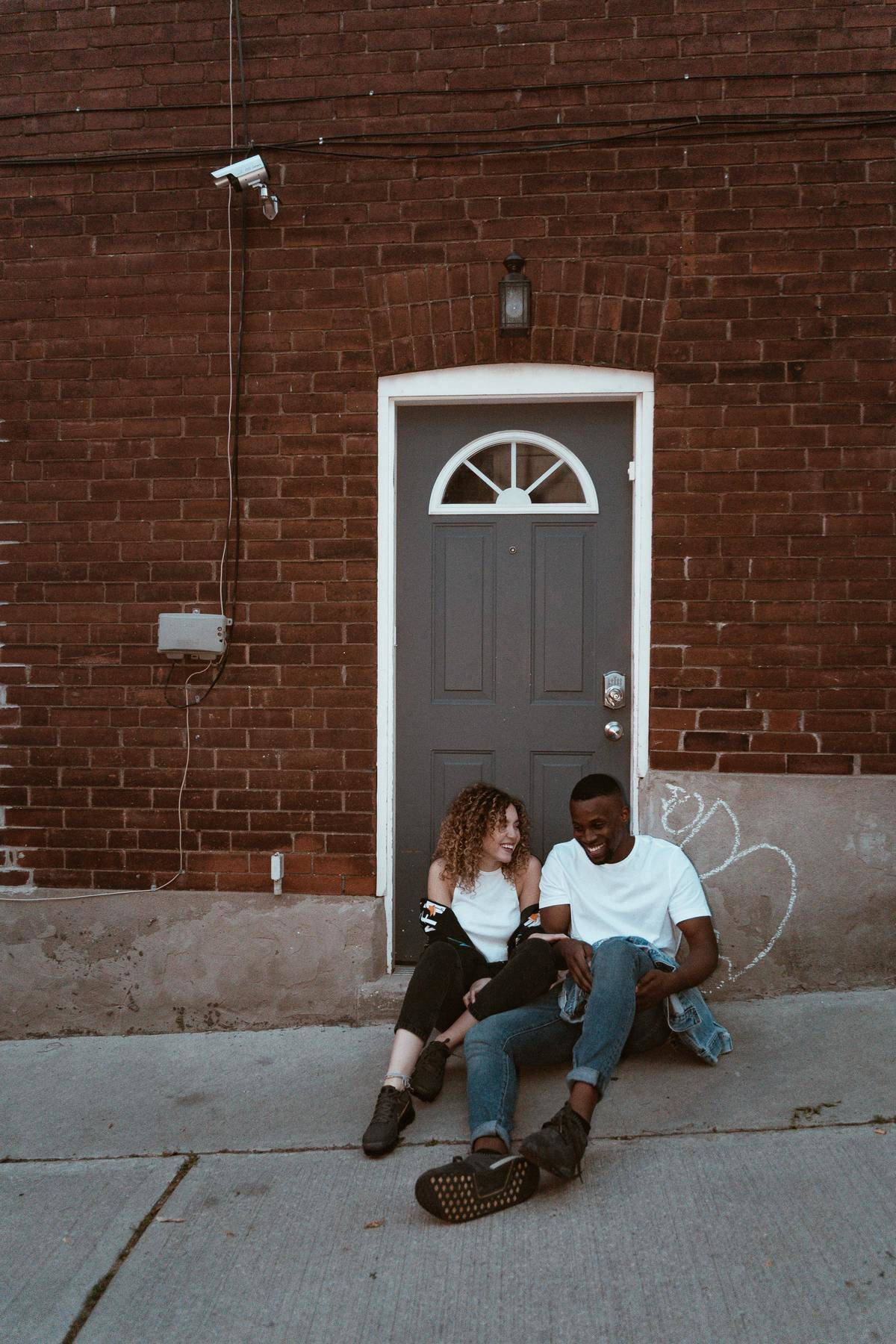 couple on a date sitting by a door laughing