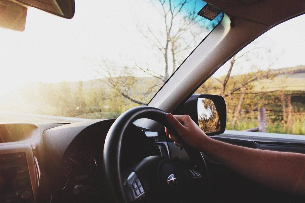 woman driving car sun shining through windshield