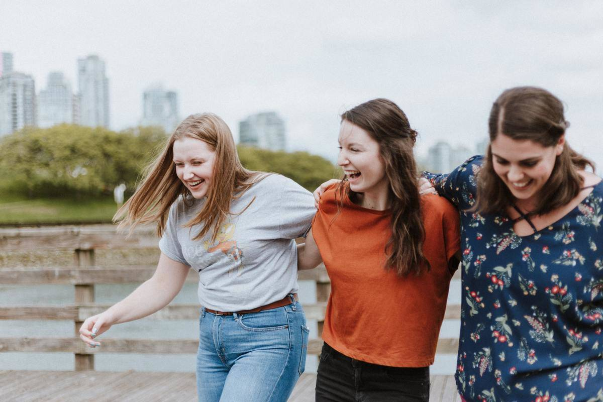 group of three female friends walking laughing outside