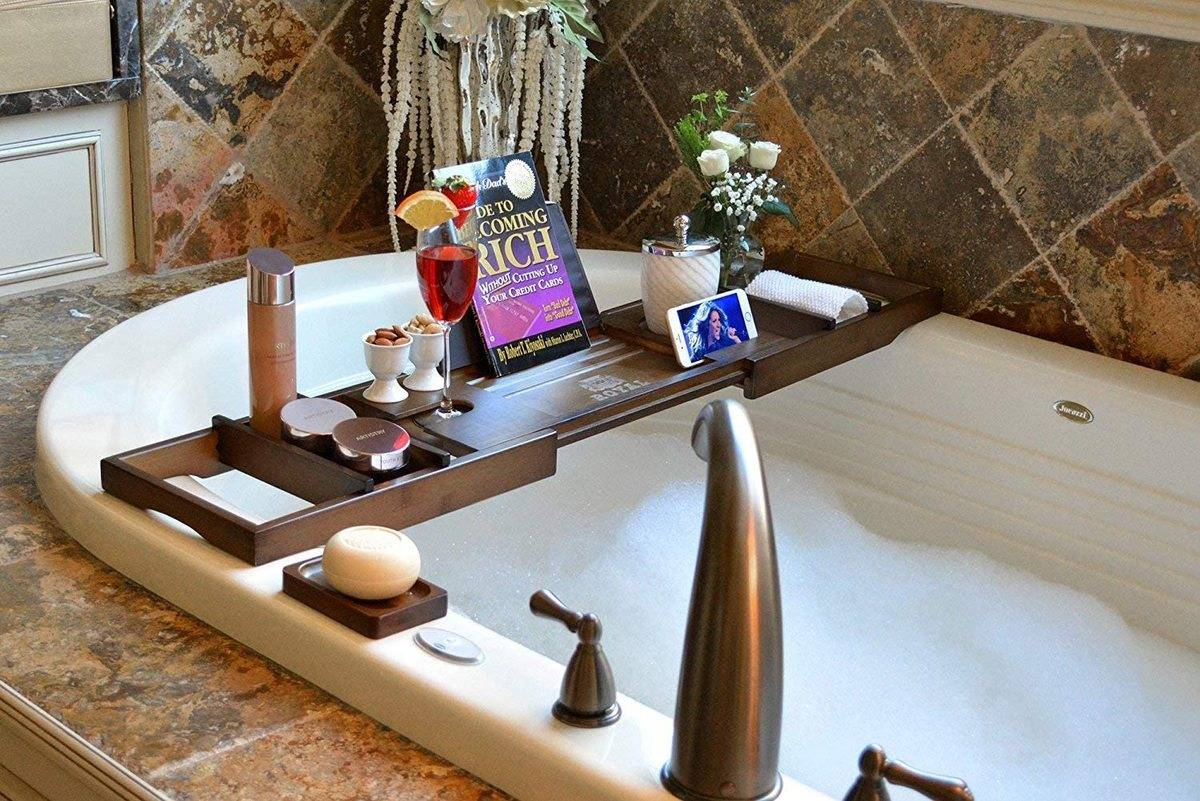 tray laying on bathtub edges with book, champagne, plant, phone etc