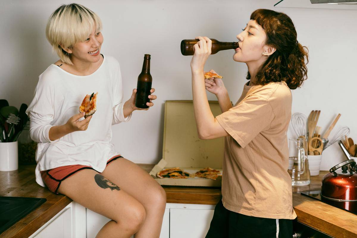 two women eating pizza drinking out of bottles at home