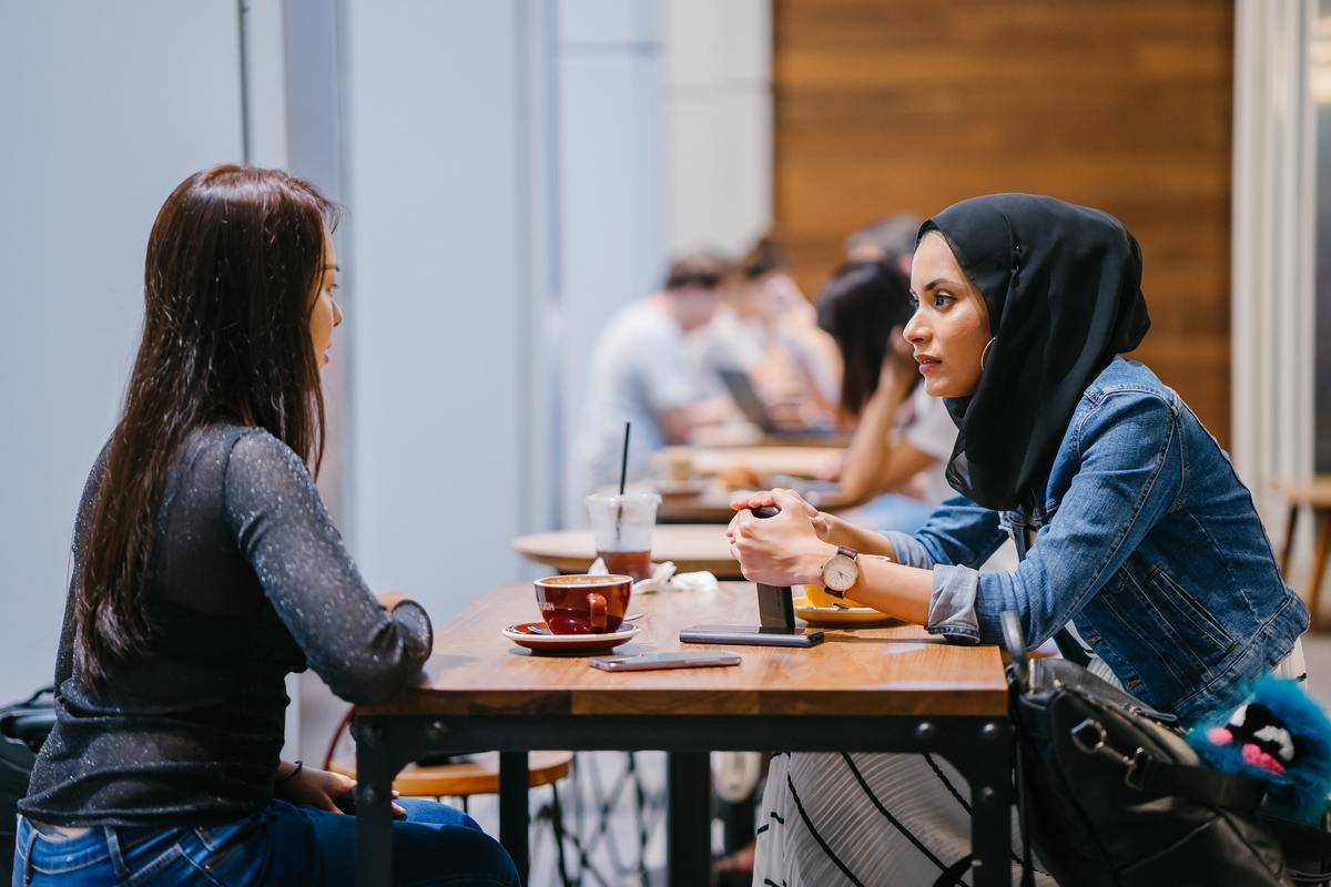 two women seated inside a cafeteria having discussion