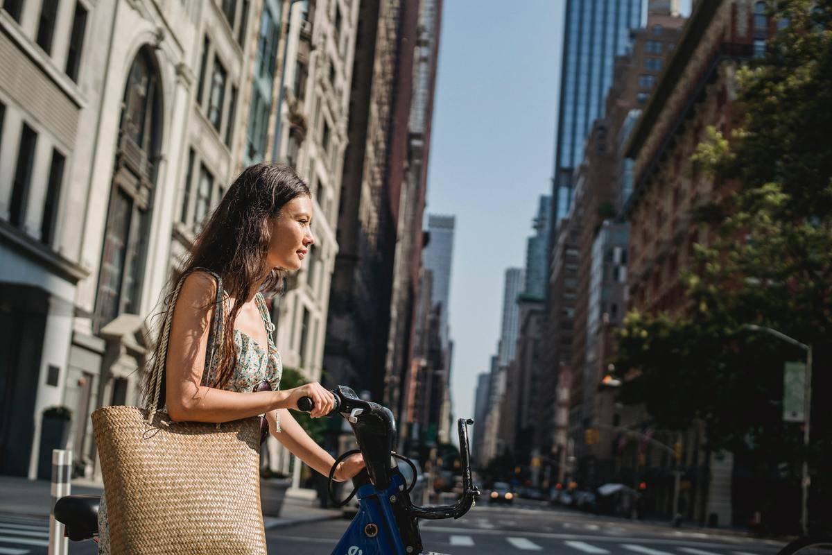 woman walking bike along sidewalk crosswalk in sunshine