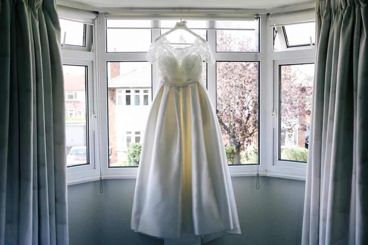 wedding dress hanging in window of house
