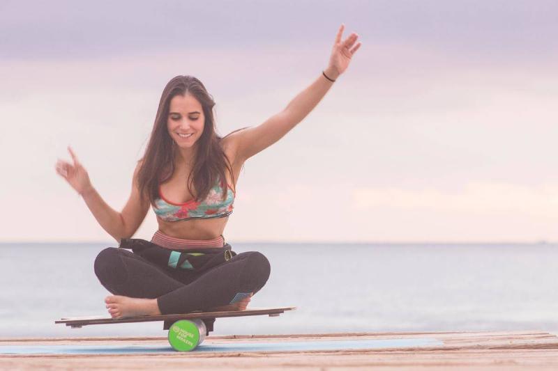 woman balances on board by a beach