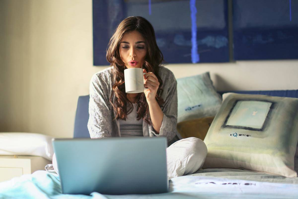 woman drinking coffee while watching tv in bed