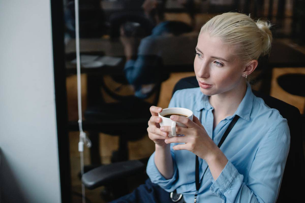 woman drinking tea looking away in thought