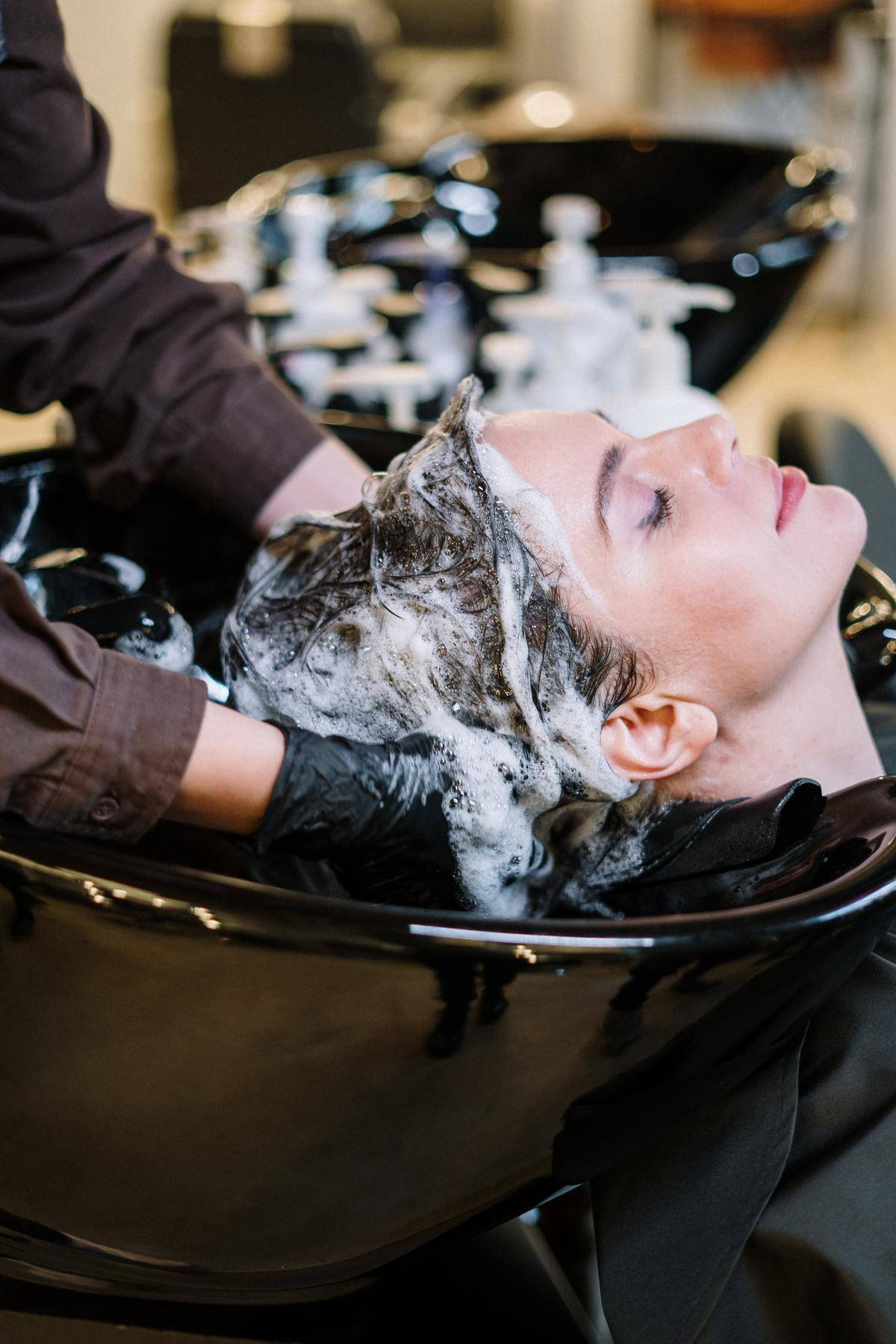woman getting hairwashed in sink by hairdresser