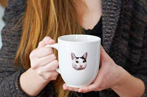 woman holding mug with cat sticker