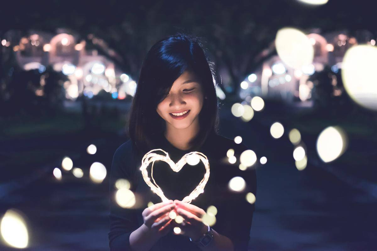 woman holds lit hearts in the park