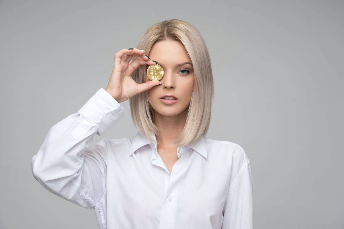 woman in white dress shirt holds up coin to her eye