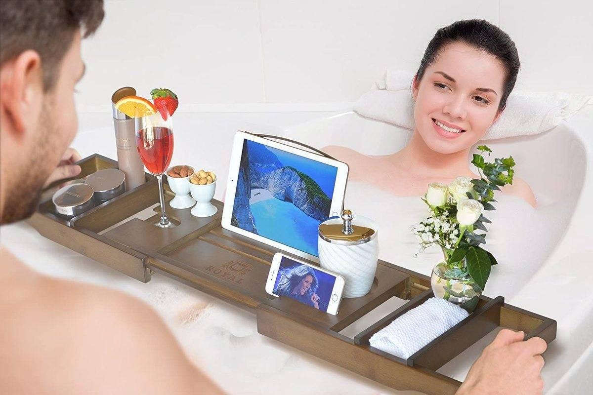 man hands woman in bath tube her fancy bath tray
