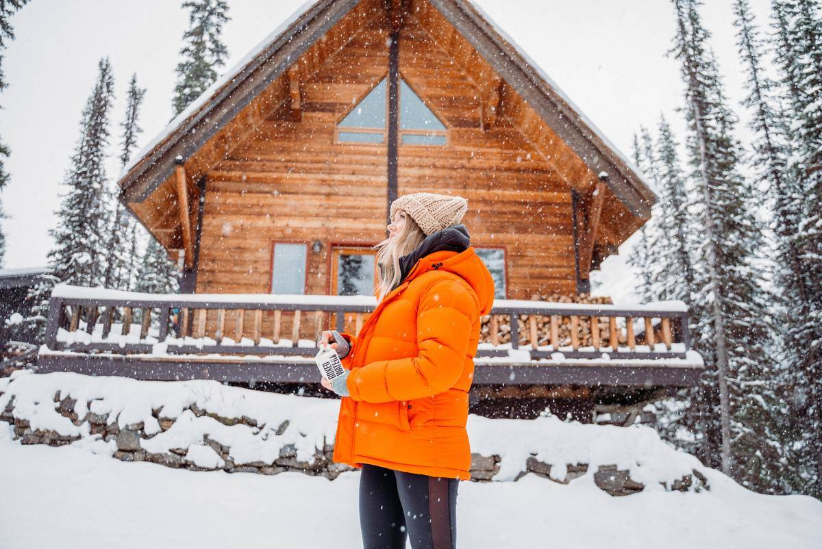 woman stands in front of wooden house in the snow