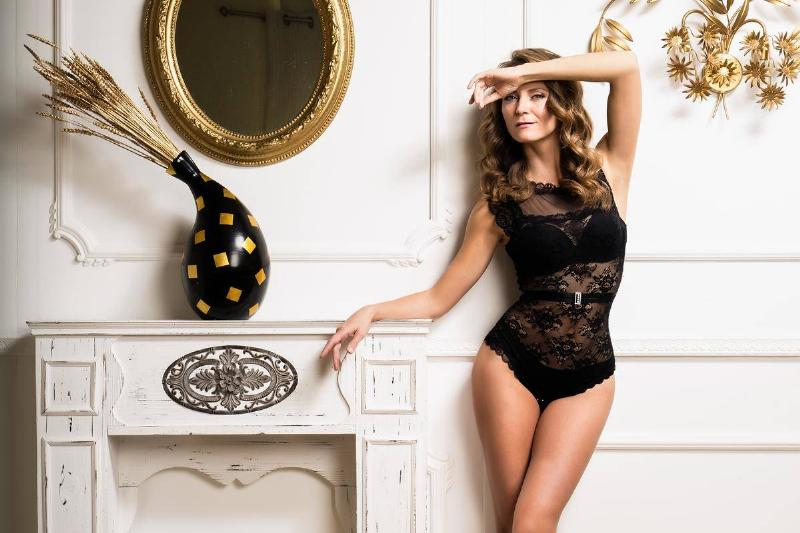 woman stands in lingerie by the fireplace