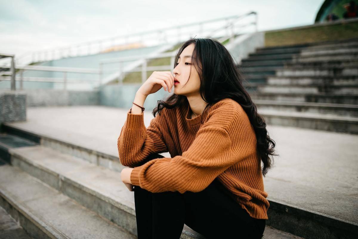 woman in orange sweater seated on bleachers alone thinking