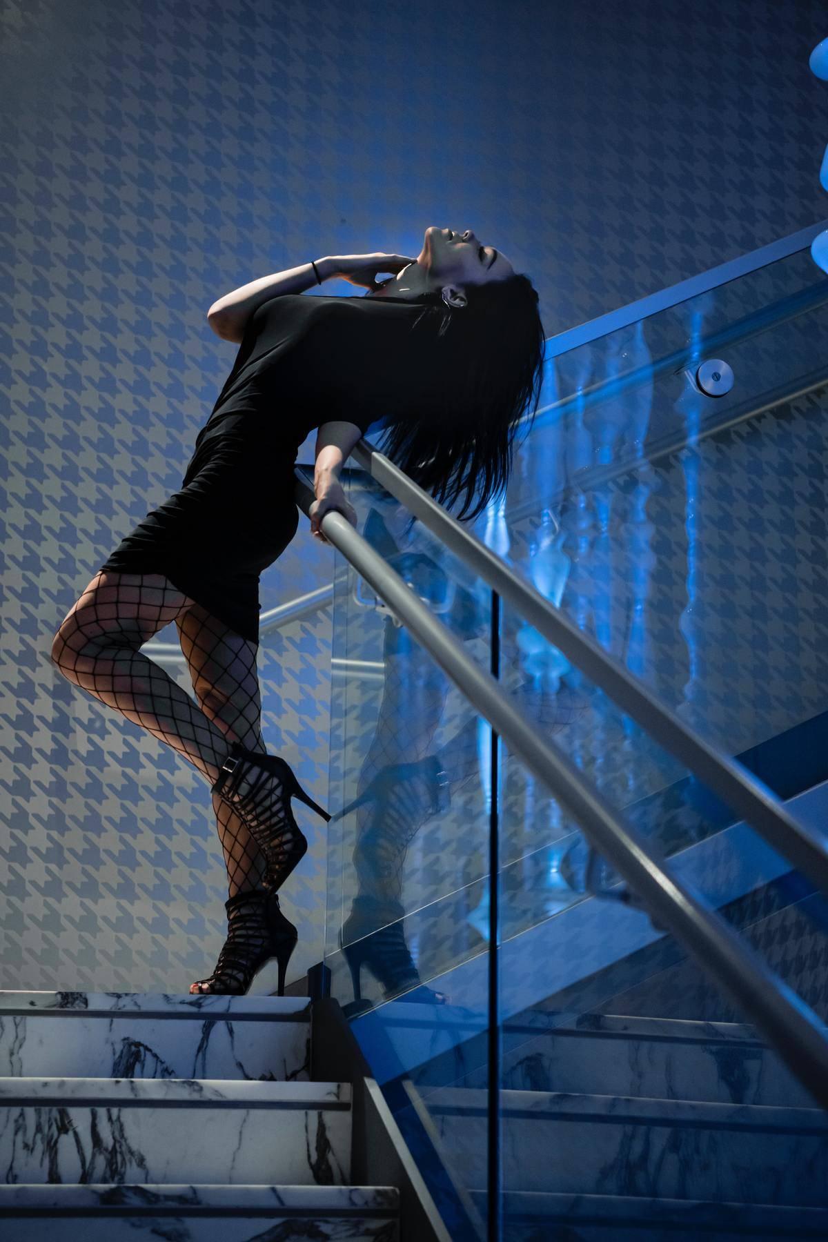 woman in stockings leaning against stairway in blue lighting