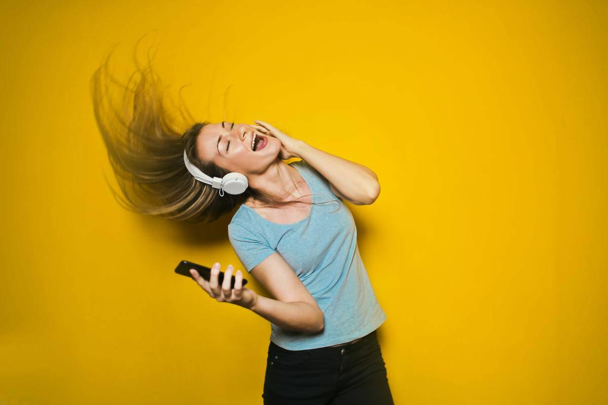 woman jamming to music in front of yellow wall