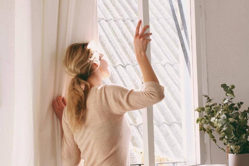 woman looking out of open window