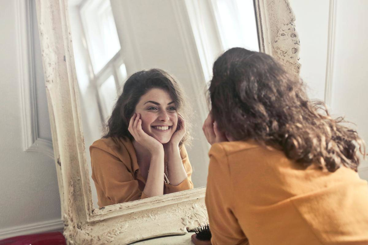 woman looks at her reflection in the mirror and smiles