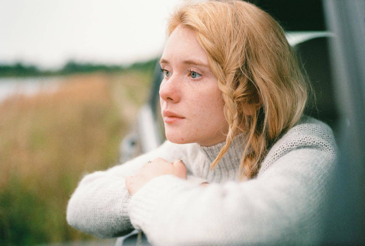 woman looks out car window into a field