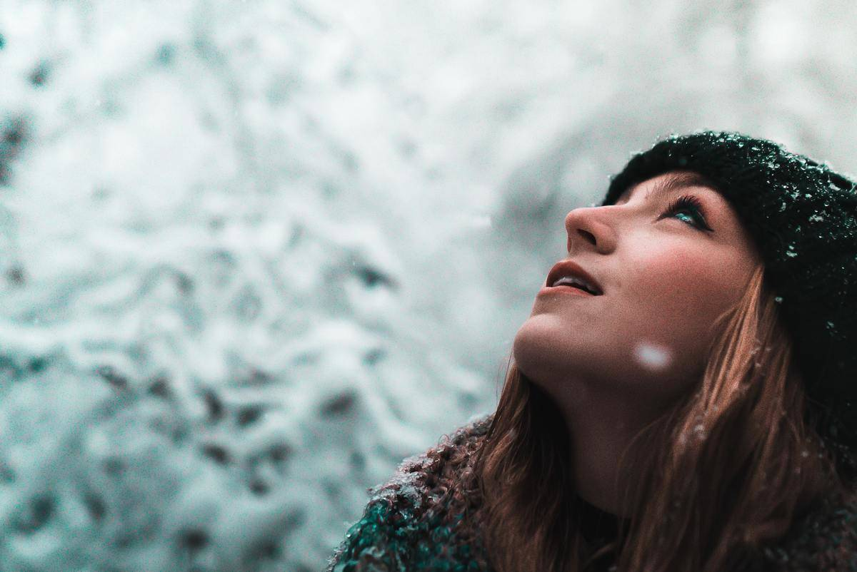woman looks up to the sky in the snow