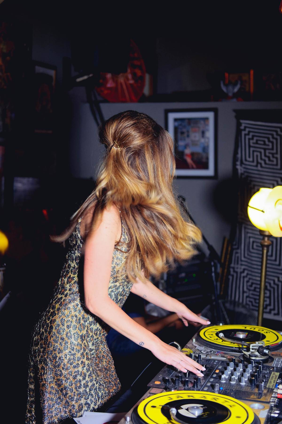 woman in party outfit plays with dj table