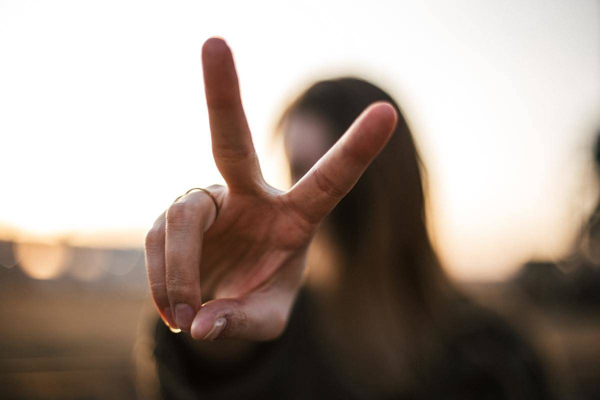 woman shows off peace sign close to the camera
