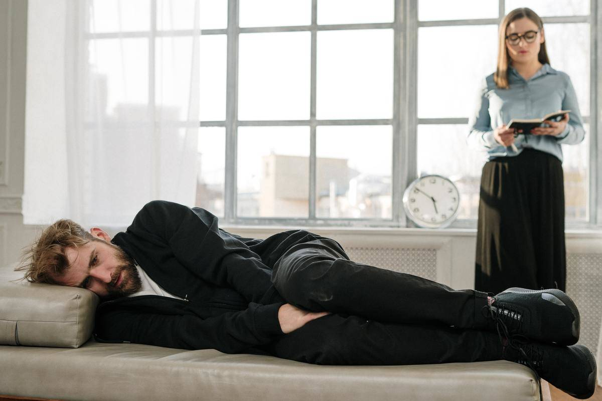woman stands over man lying down
