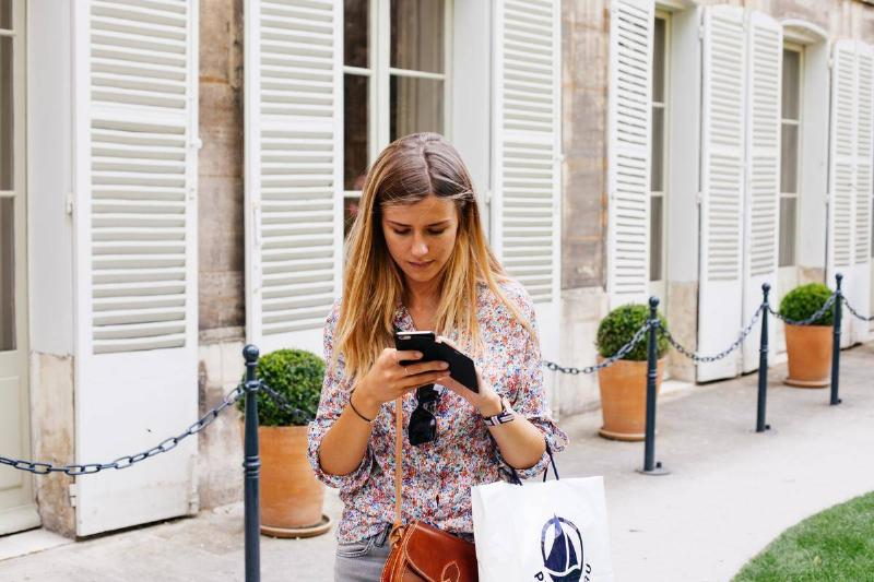 woman texting while walking outdoors