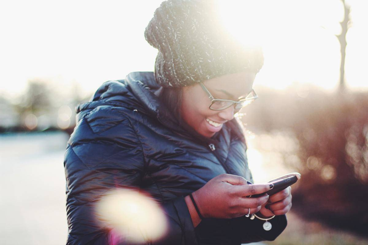 woman smiles down to phone