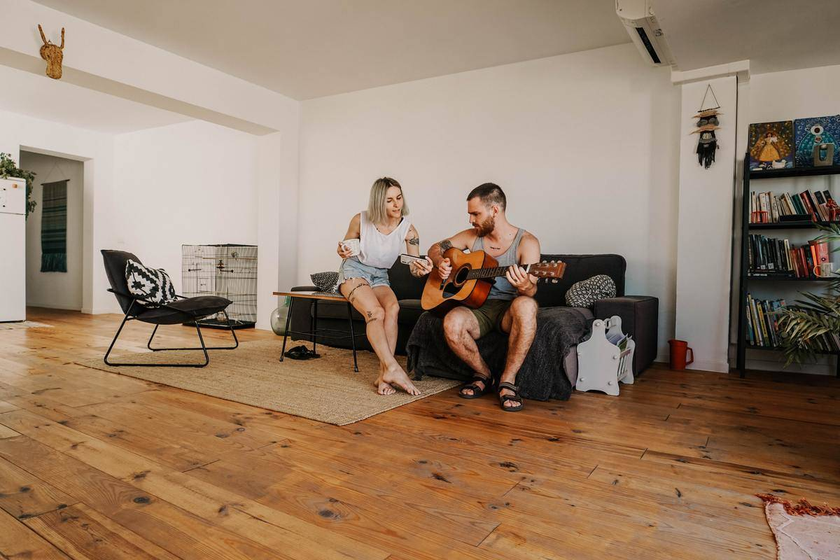 woman with man on couch playing guitar