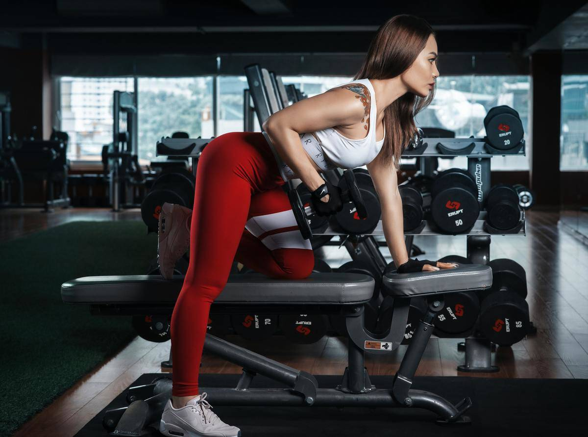 woman working out at the gym using a bench and weights