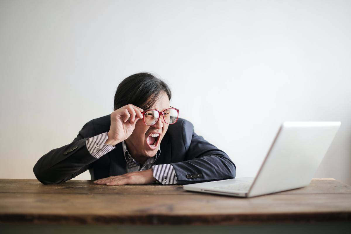 woman yelling at laptop screen in business