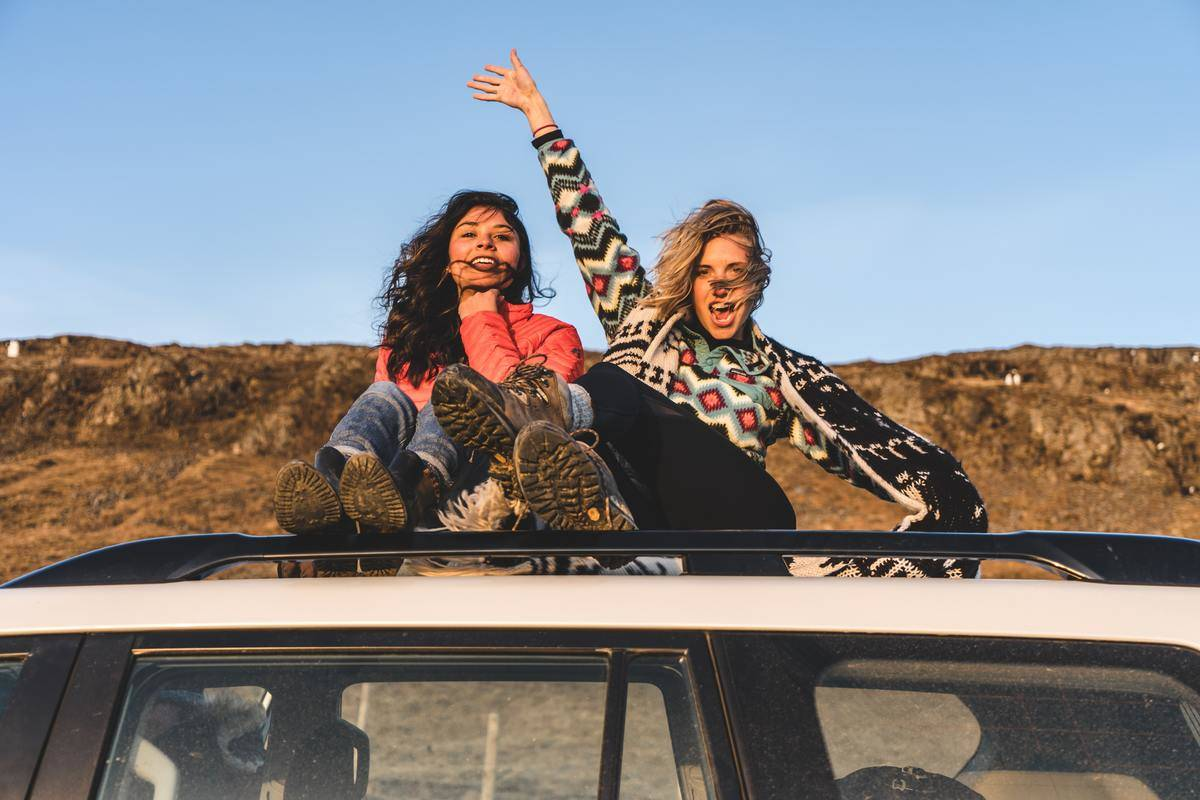 woman waves as she sits besides her friend on car roof