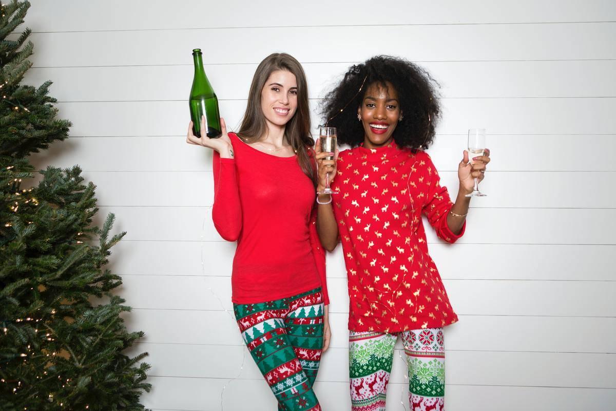 two women holding wine in christmas pyjamas