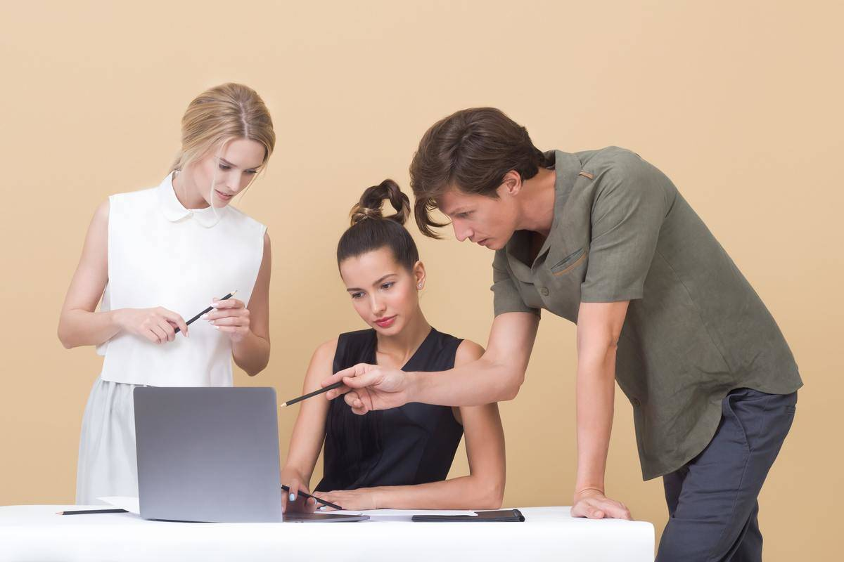 man pointing to something on female coworker's screen