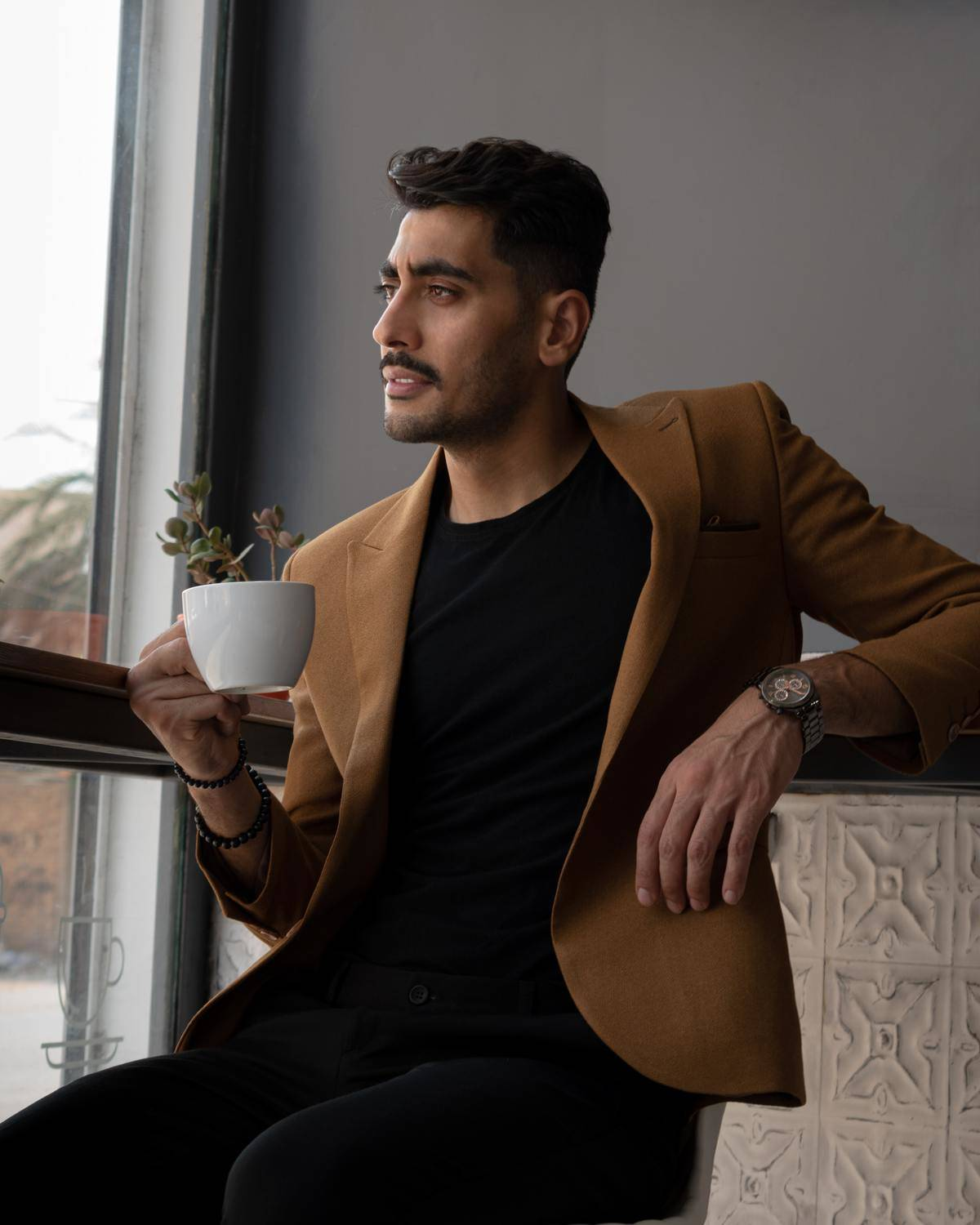 man drinking coffee by the window
