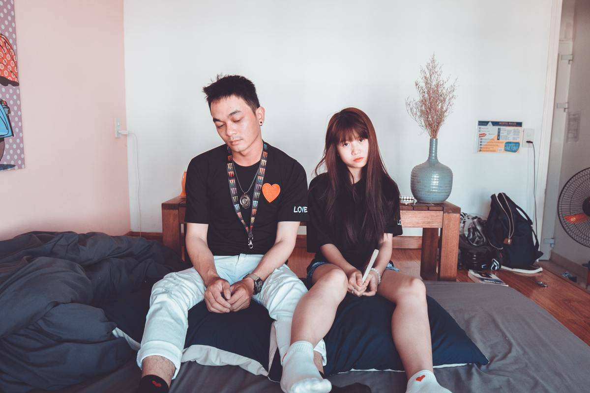 couple sits on bed looking sad