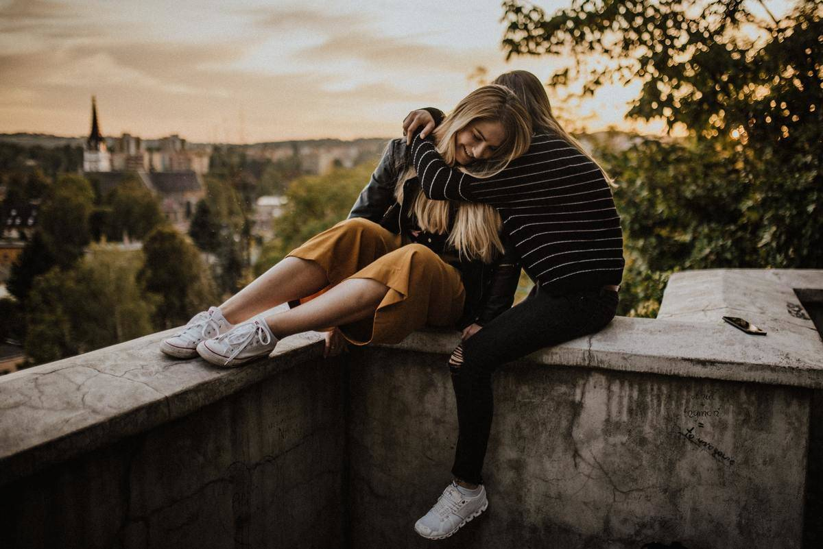 Two women hug while sitting on a ledge overlooking city