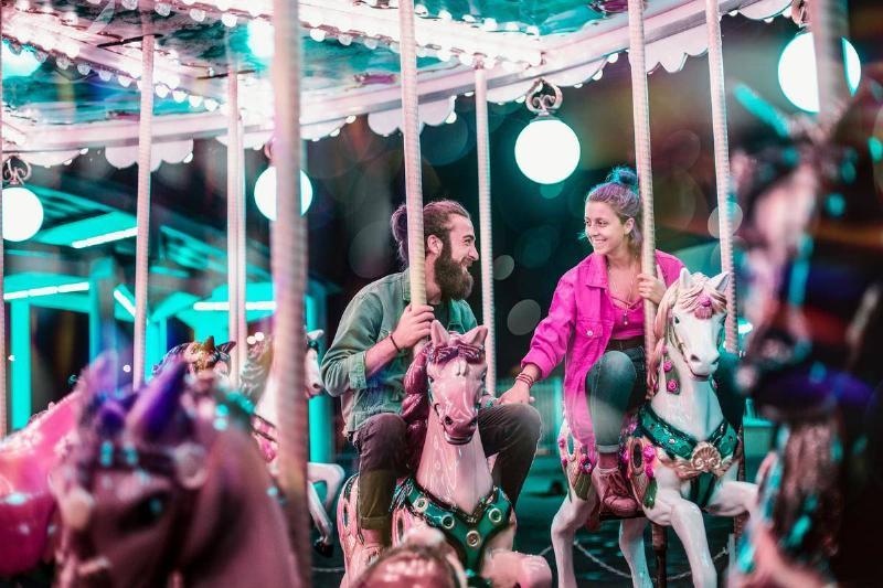 couple rides the merry go round horses
