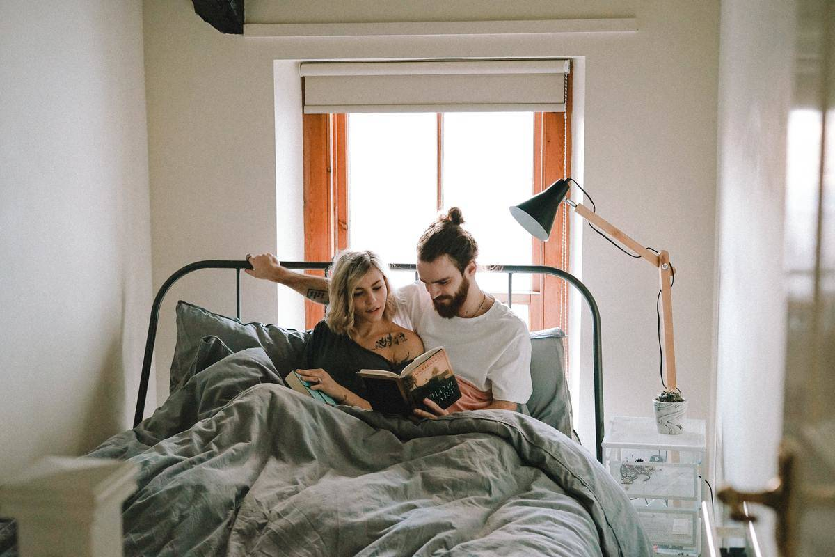 Couple reads a book in bed