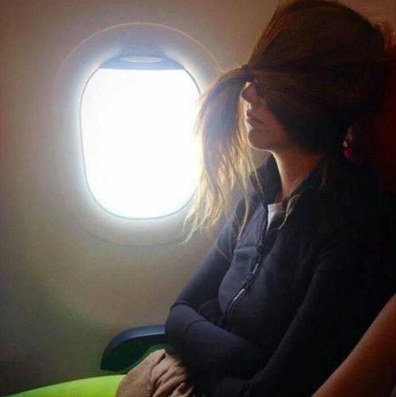 woman on an airplane with her in a ponytail over her eyes